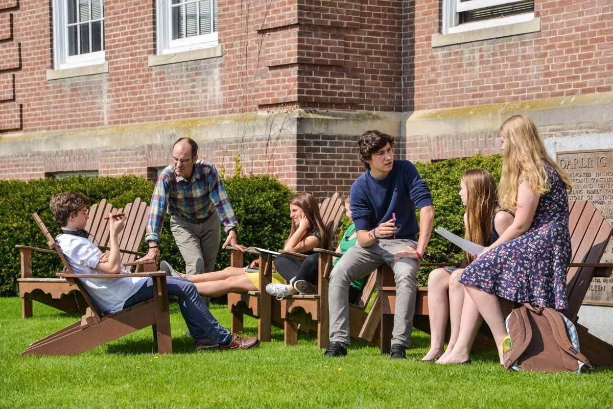 "alt=""Students engaged in a learning activity on the front lawn of our Main Building"""